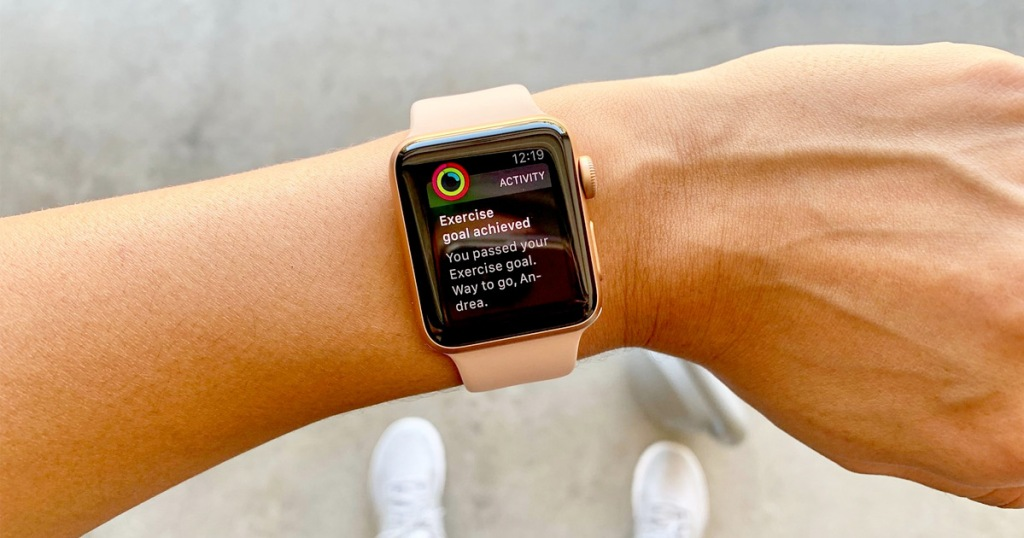 pink apple watch on wrist showing workout goal completed notification