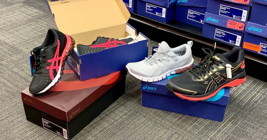 boxes of Asics brand shoes open on floor next to store display of shoe boxes