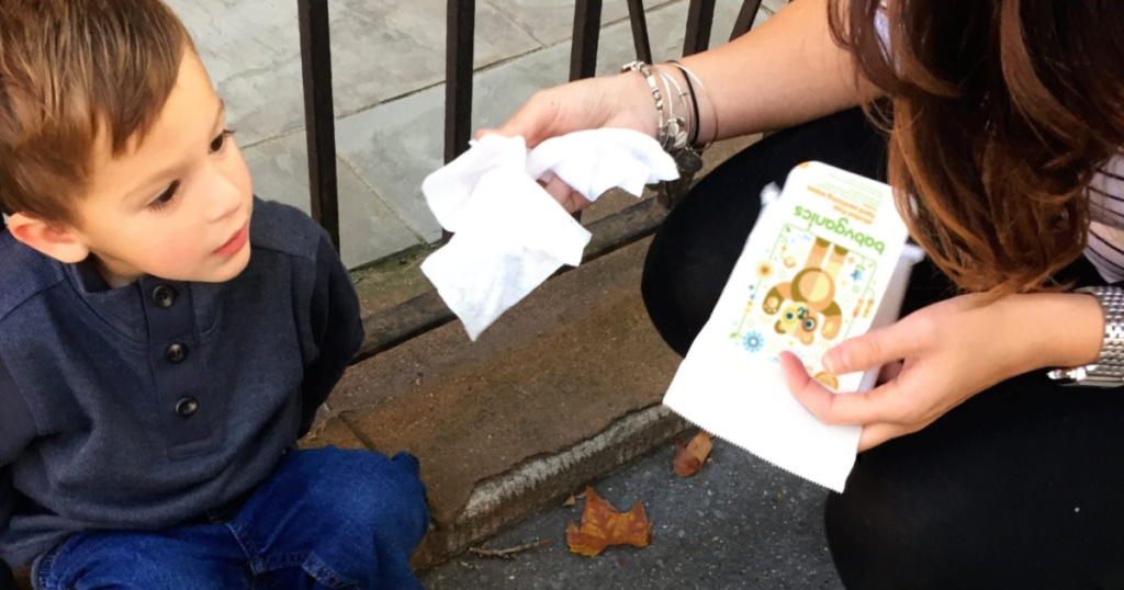 woman holding wipes handing one to a little boy