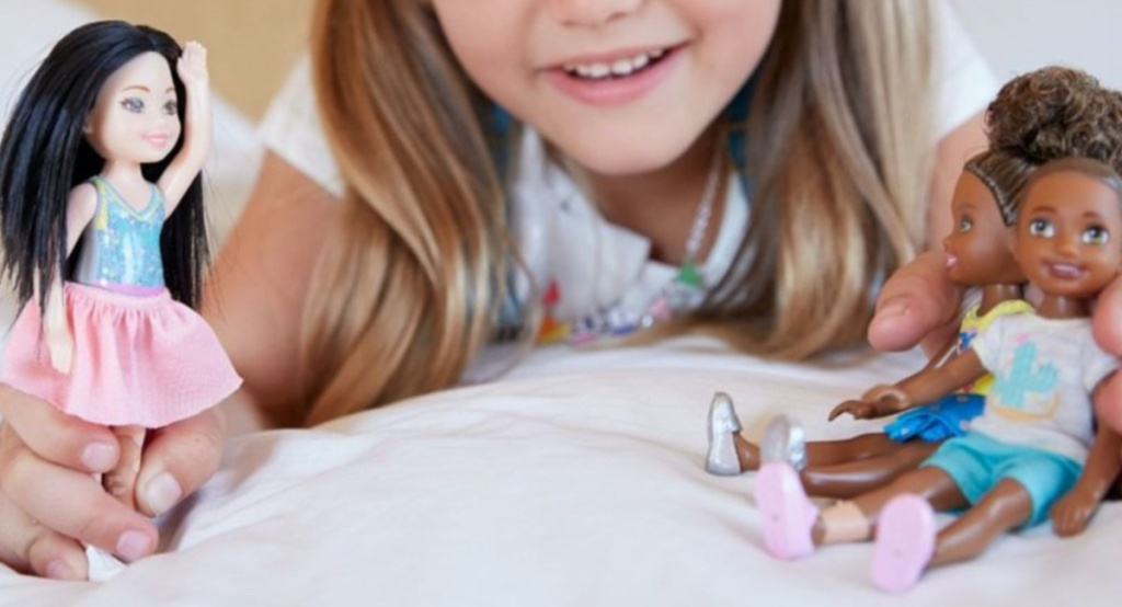 girl playing with three dolls on bed