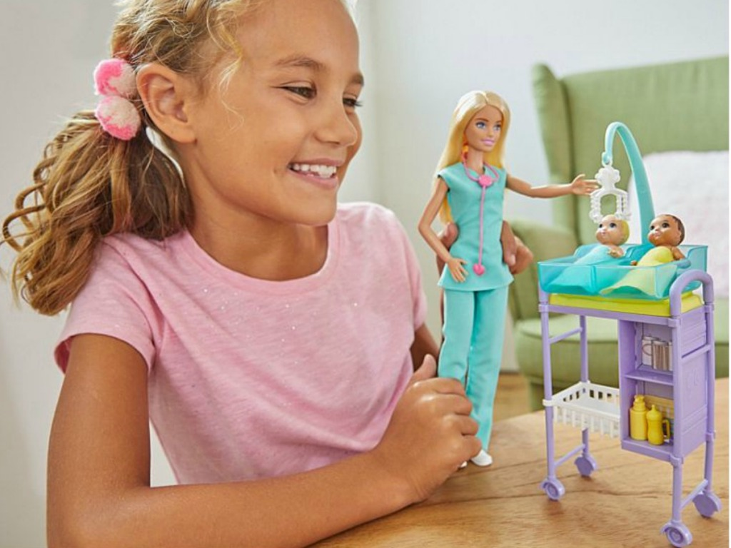girl playing with Barbie Nurse Doll
