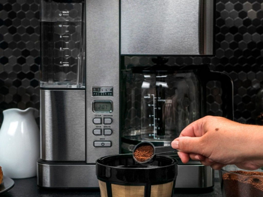 stainless steel coffee maker on kitchen counter and hand scooping coffee grounds