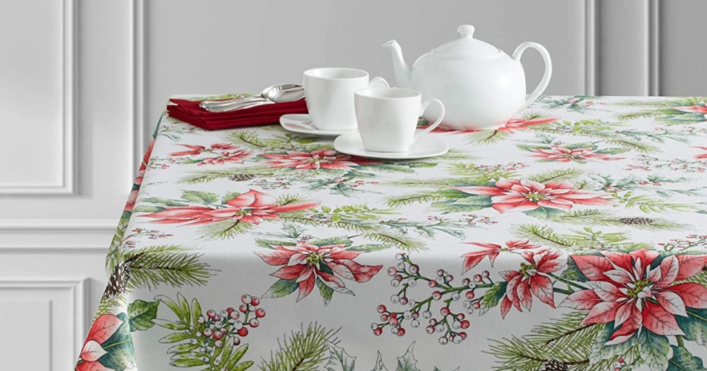 poinsetta tablecloth on table with white tea pot, cups, and plates on top