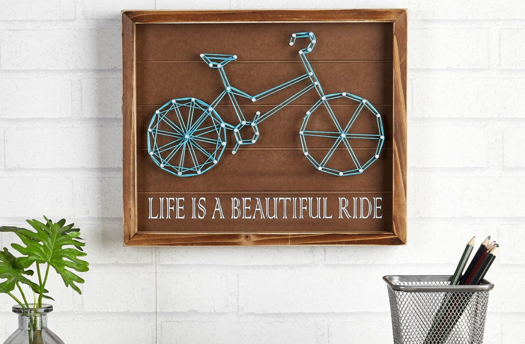 wall art made with string to shape a bike that reads life is a beautiful ride