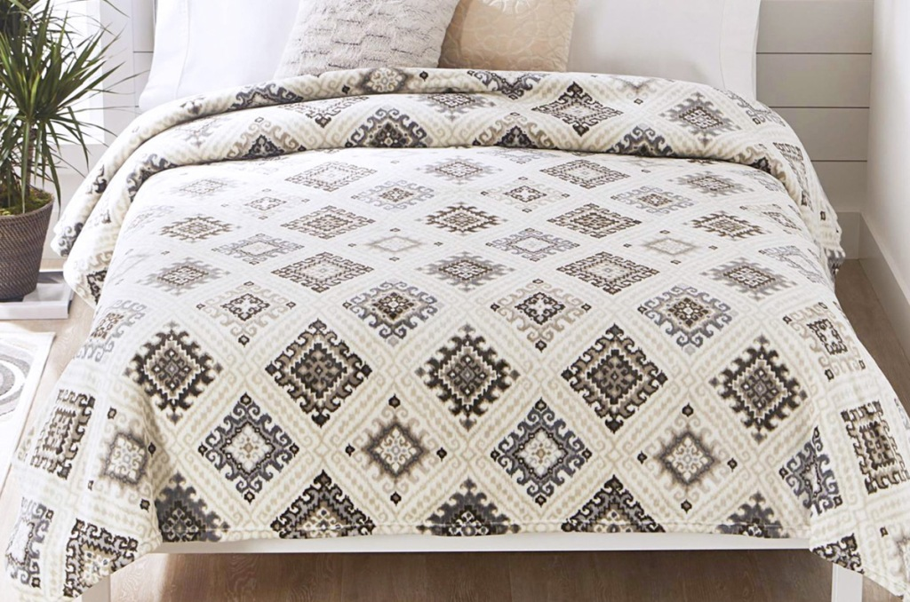 white plush blanket with brown diamond pattern on a bed