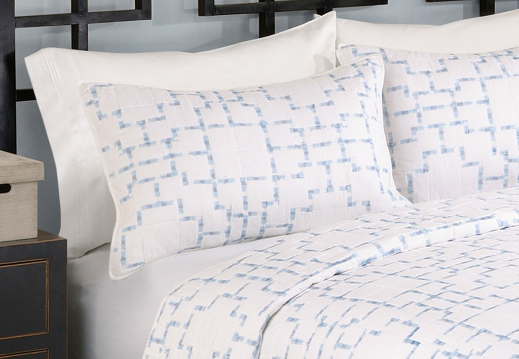white pillow shams with light blue print on a bed with matching duvet