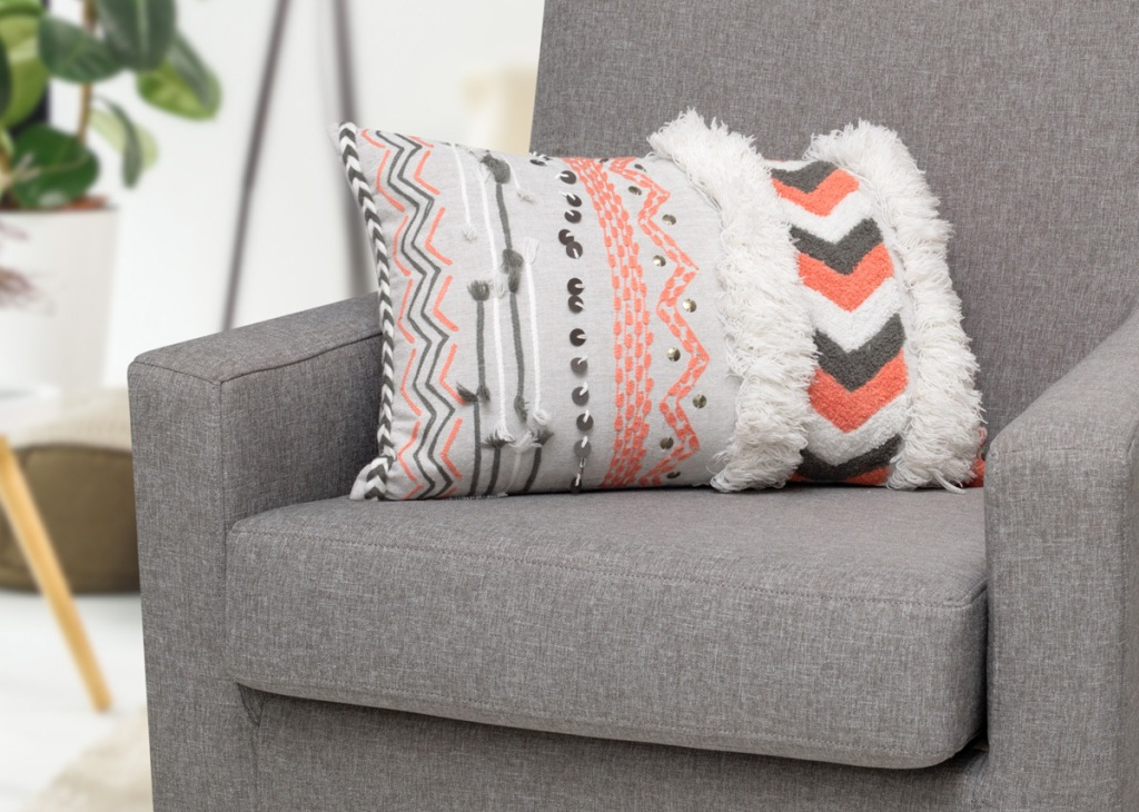 white throw pillow with grey and pink abstract chevron prints sitting on a grey chair