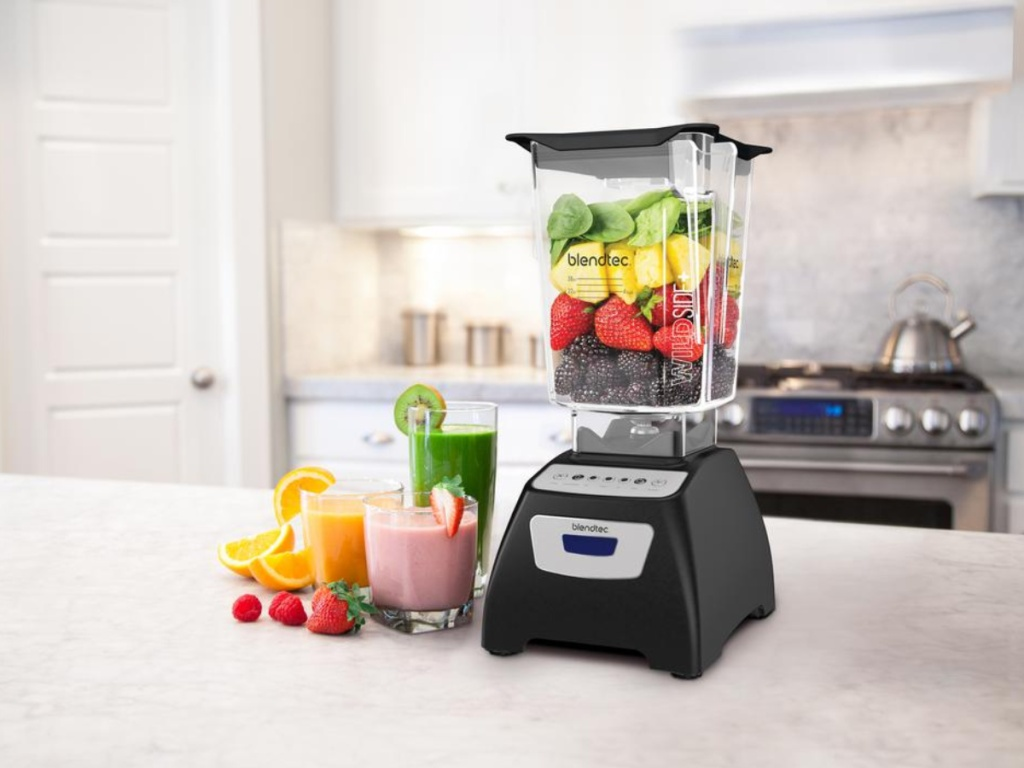 blendtec blender with fruit in blender and smoothies beside it on counter