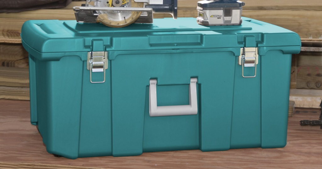 teal colored plastic storage trunk with silver handle and power tools sitting on top of lid