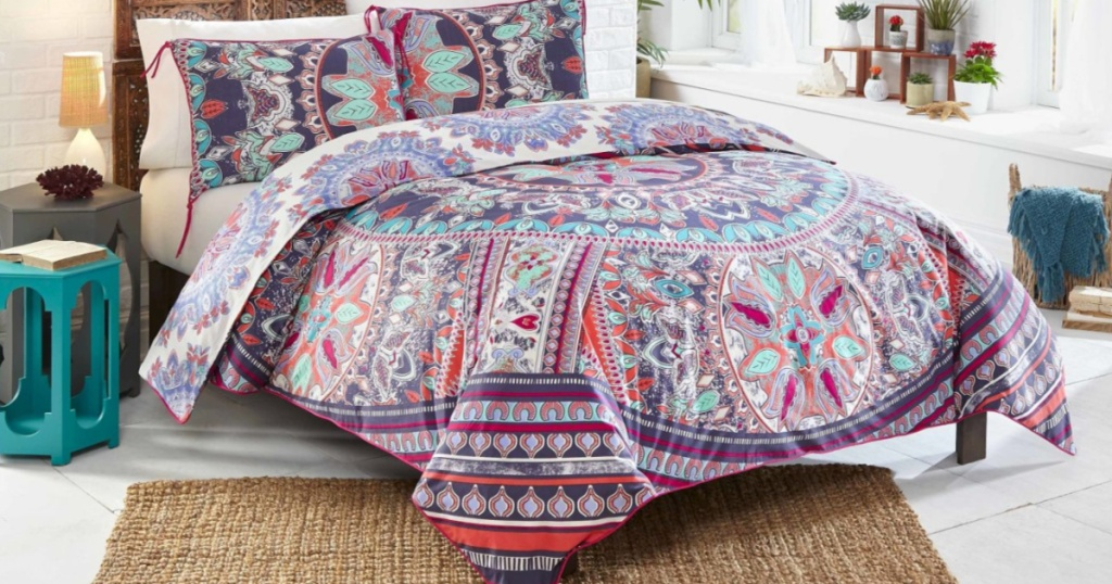 colorful comforter with matching shams on bed in bedroom