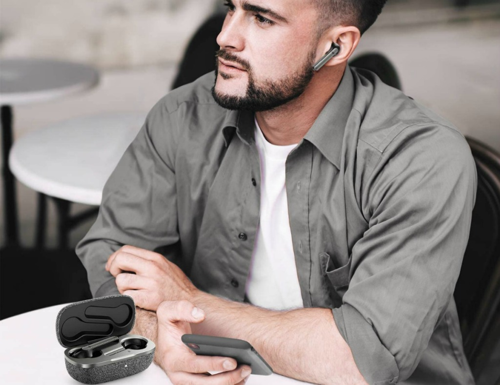 man wearing wireless earbuds and holding a phone