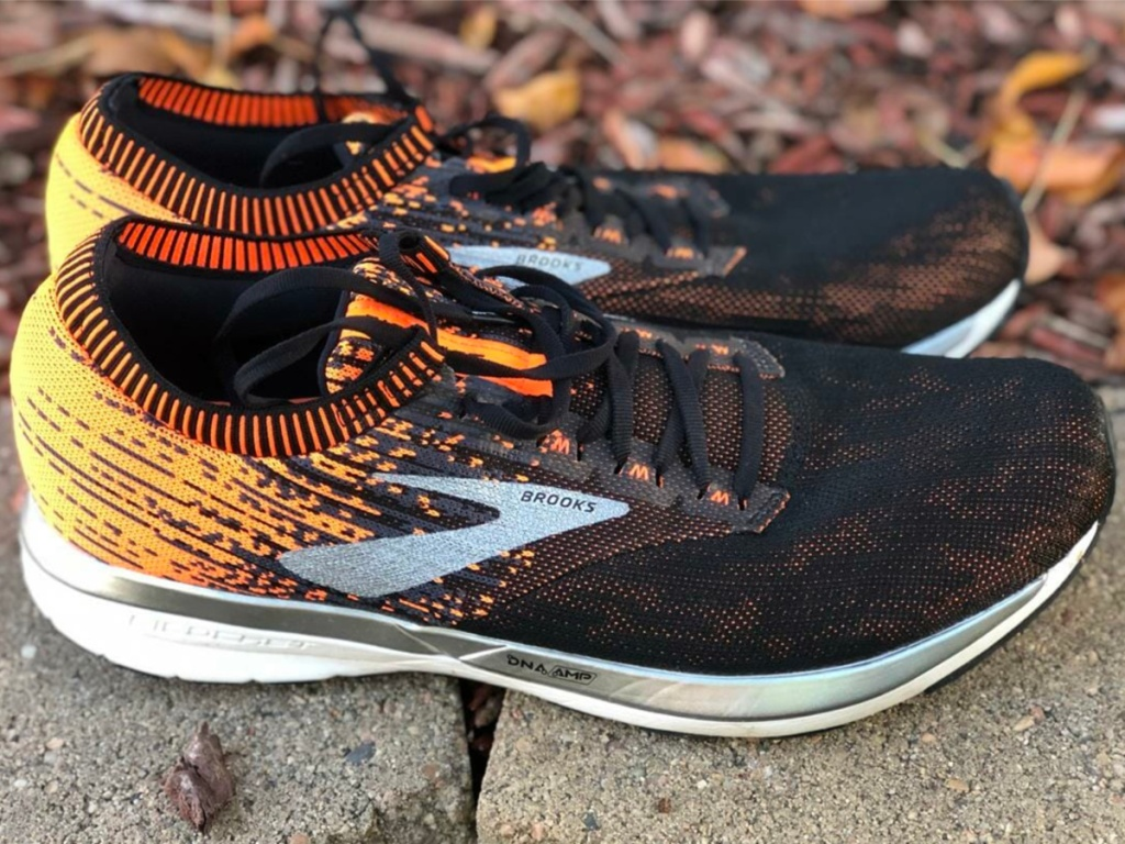 men's black and orange sneakers on rock outside