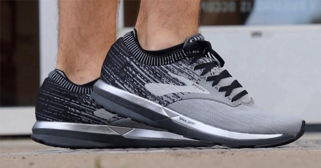 feet in men's black and grey sneakers