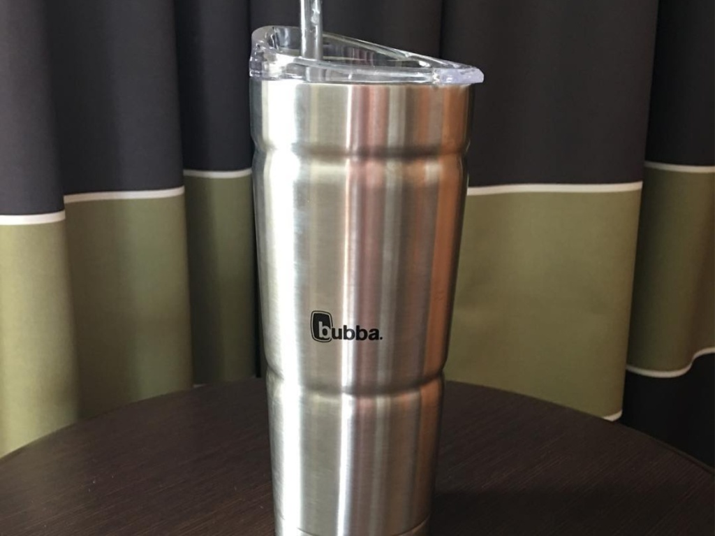 stainless steel tumbler with clear straw on wood table