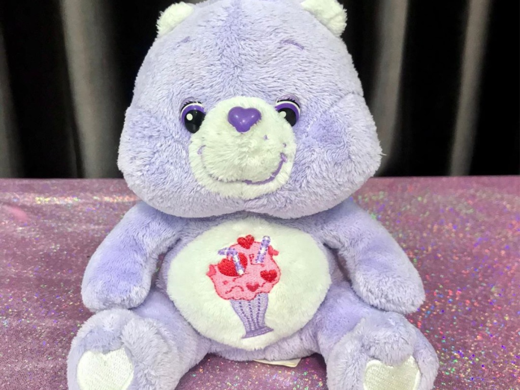 purple plush bear with hearts and milkshake design on stomach on purple tablecloth