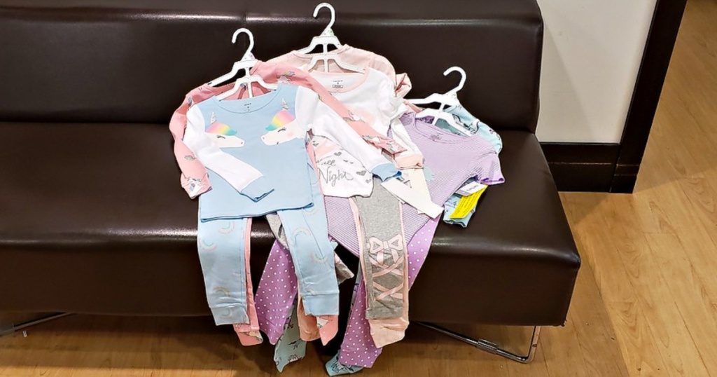 Carter's Girls Pajama Sets on hangers on couch