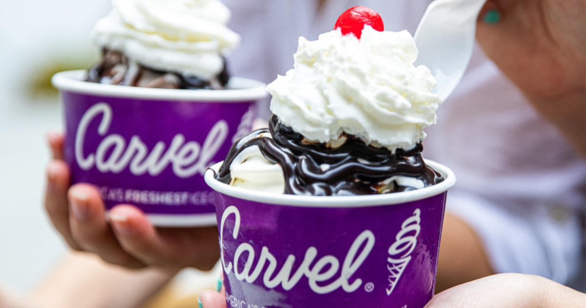 hand holding two carvel ice cream sundaes with whipped cream and cherries on top