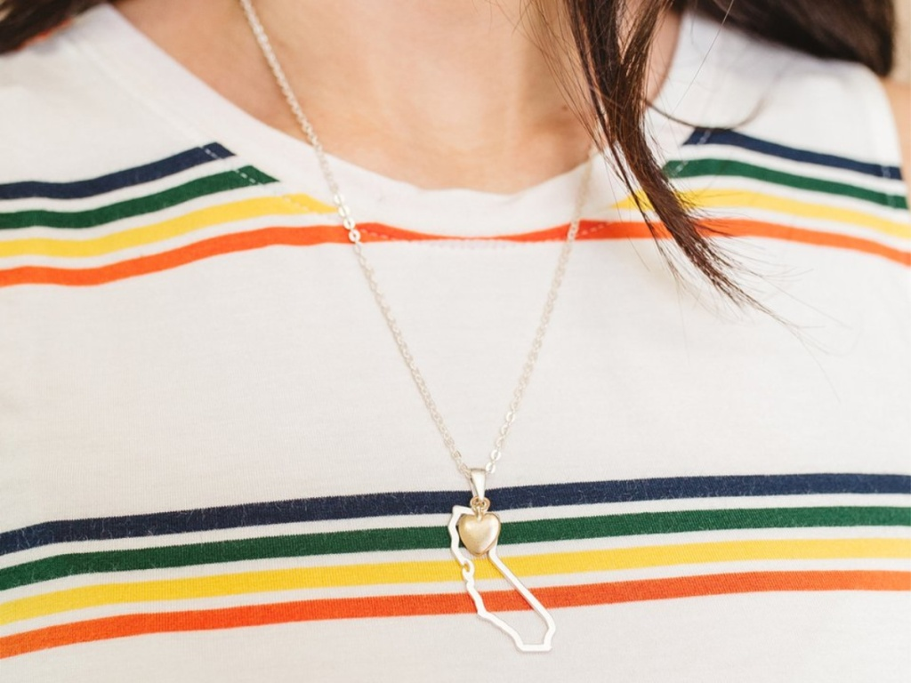 woman in white multi-colored striped shirt wearing California state pendant necklace