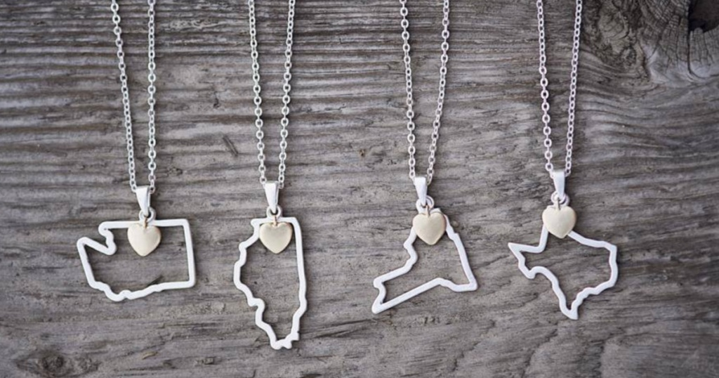 four state pendant necklaces against grey wood