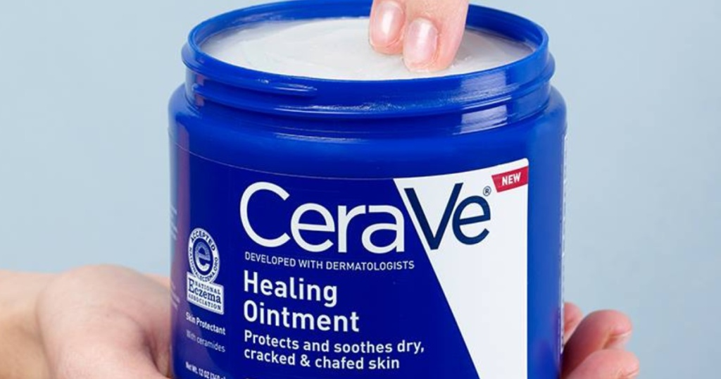 hand holding a jar of cerave ointment and two fingers dipping into the jar