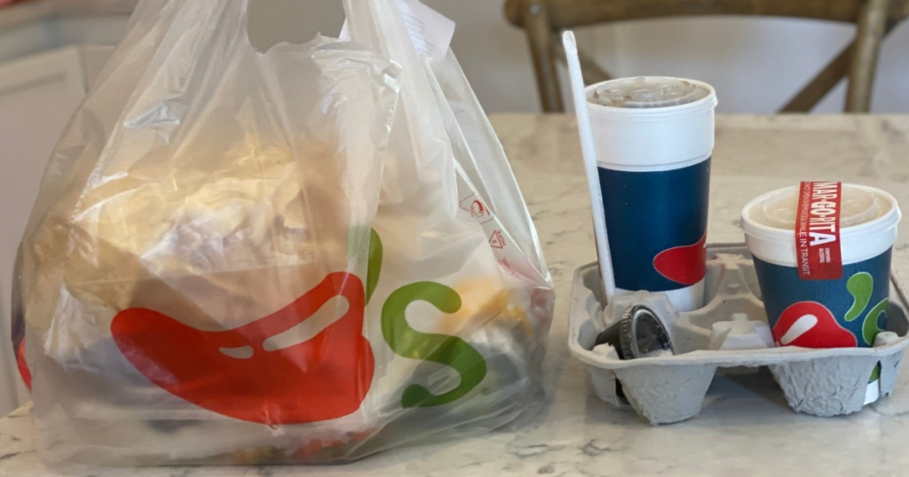 chili's takeout bag and two drinks sitting on a kitchen counter