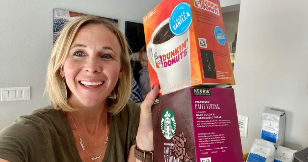 woman smiling and holding two boxes of coffee pods