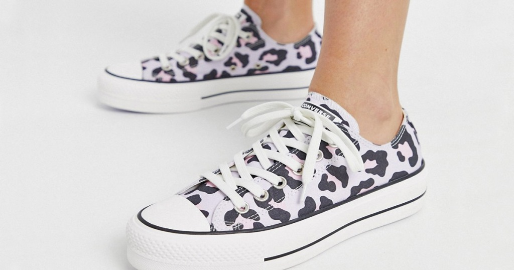 person wearing a pair of converse platform sneakers in purple and pink leopard print