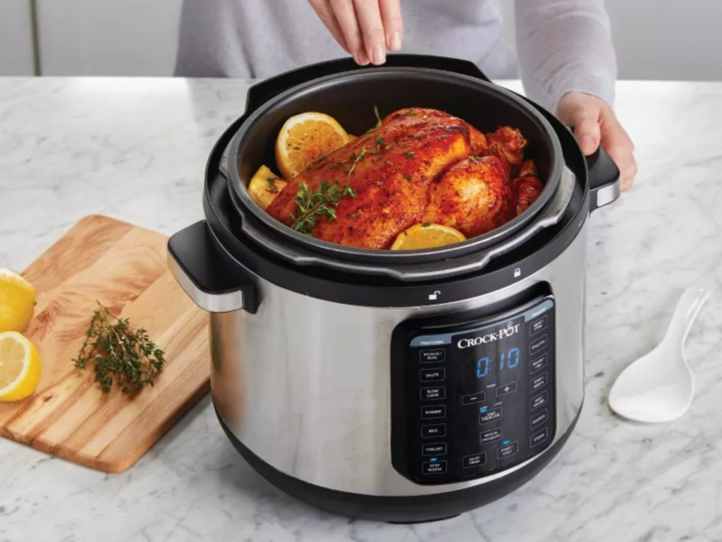 hand sprinkling seasonings on a chicken sitting into a crock pot express multi cooker