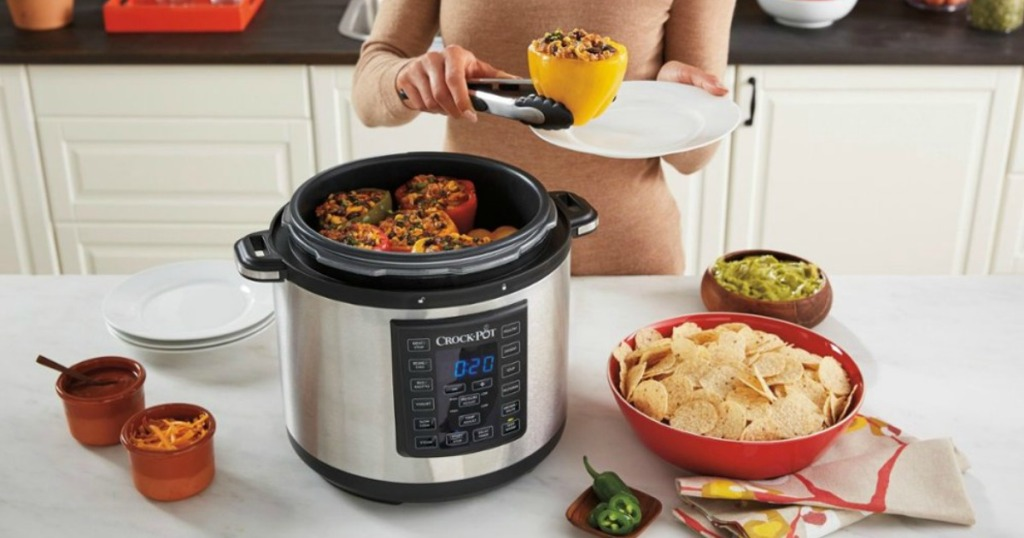 Zojirushi NS-ZCC10 Rice Cooker woman holding a stuffed bell pepper with tongs over a plate next to a full crock-pot