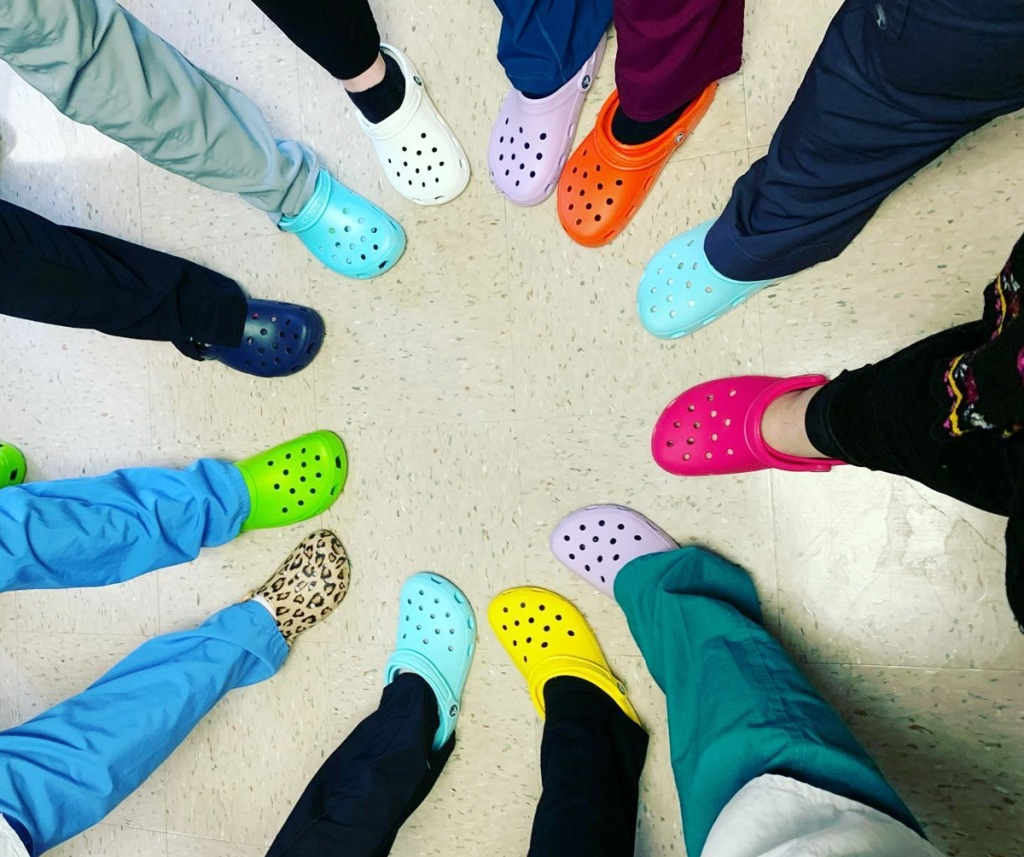 people wearing scrub pants and crocs sticking out their feet to form a circle