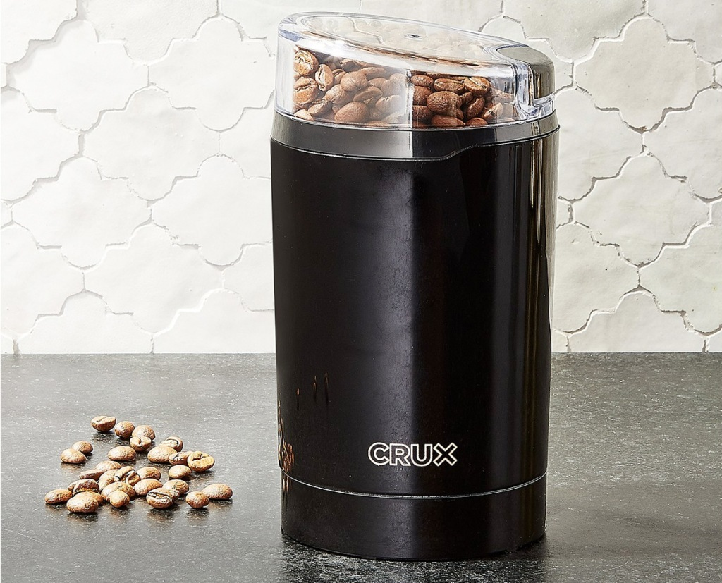 black coffee grinder with coffee beans inside sitting on kitchen counter