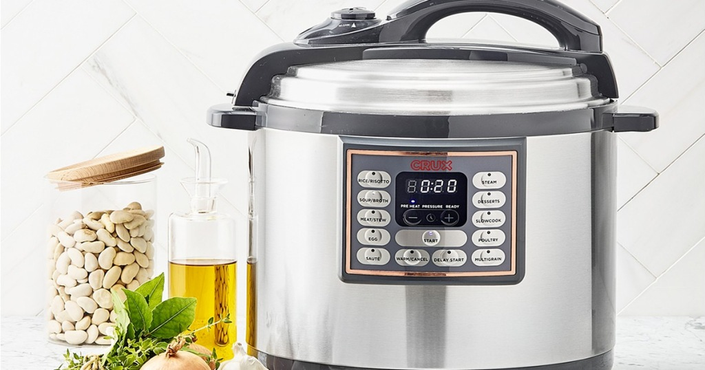 stainless steel and black pressure cooker sitting on kitchen counter