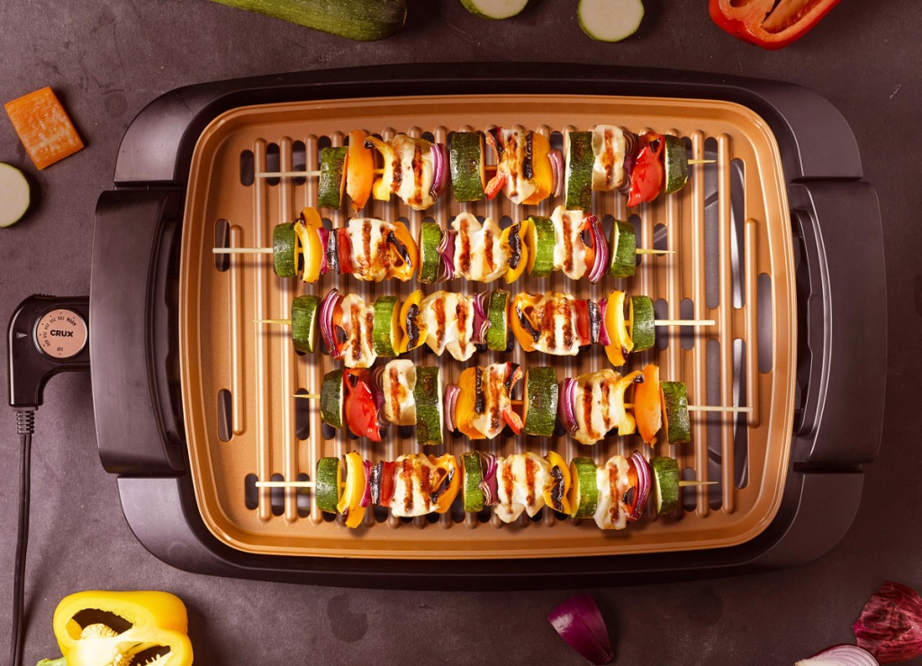copper indoor smokeless grill with vegetable kebabs on it