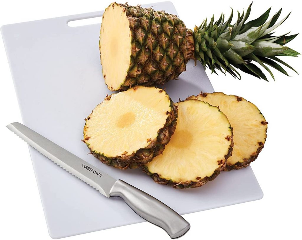 cutting board with knife and pineapple on it