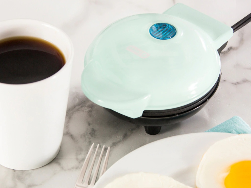 light blue mini griddle on table next to plate of eggs and white cup of coffee