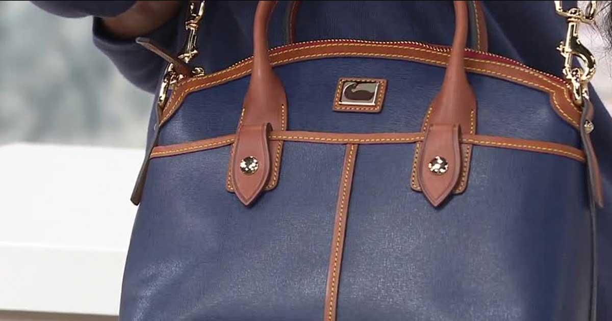 woman holding a Dooney & Bourke Camden Satchel purse