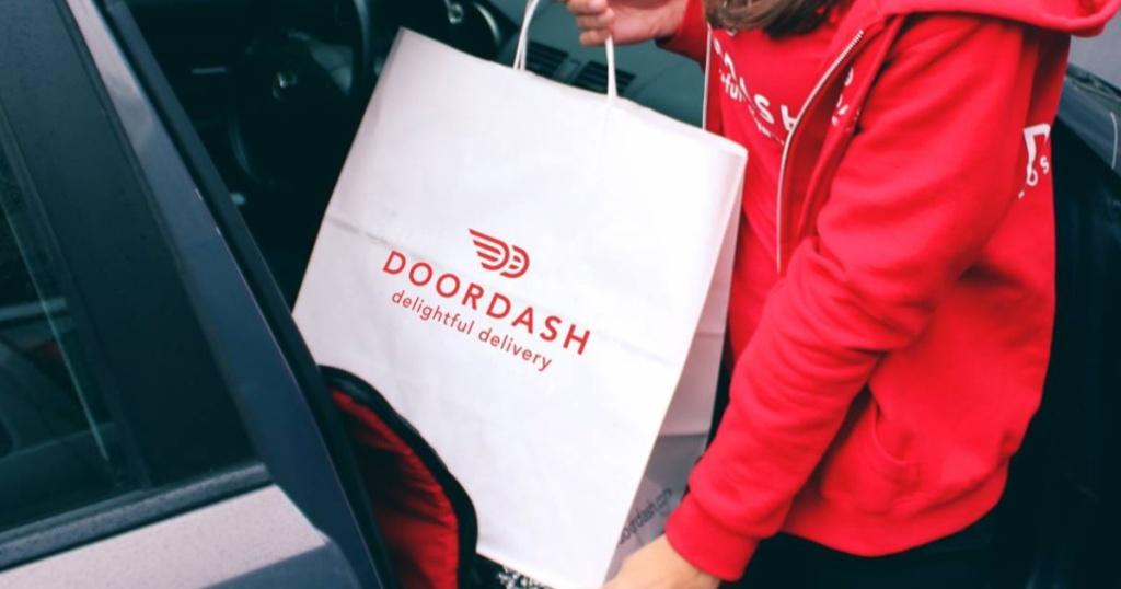 woman putting a white and red door dash bag into the front seat of her car