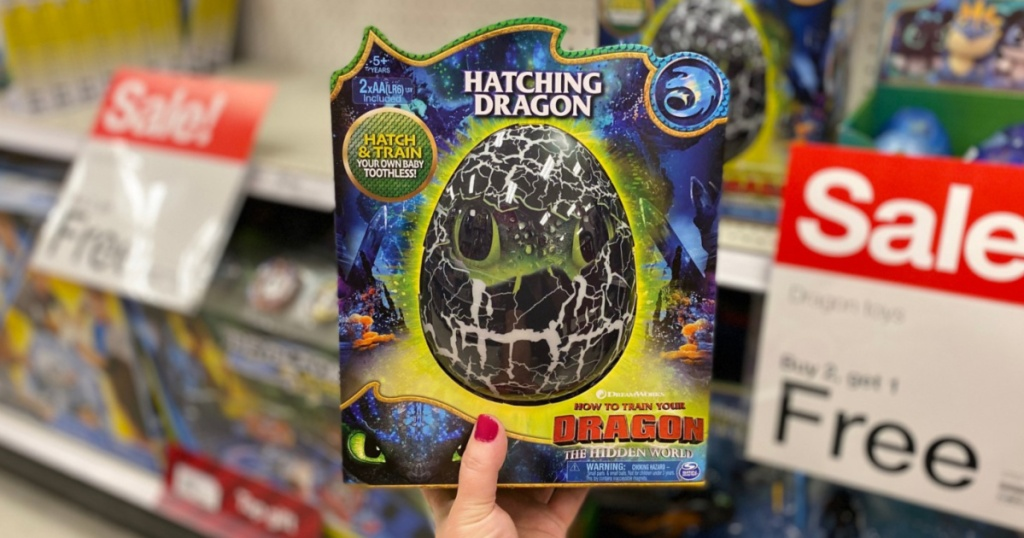 manicured hand holding hatching dragon egg toy in store