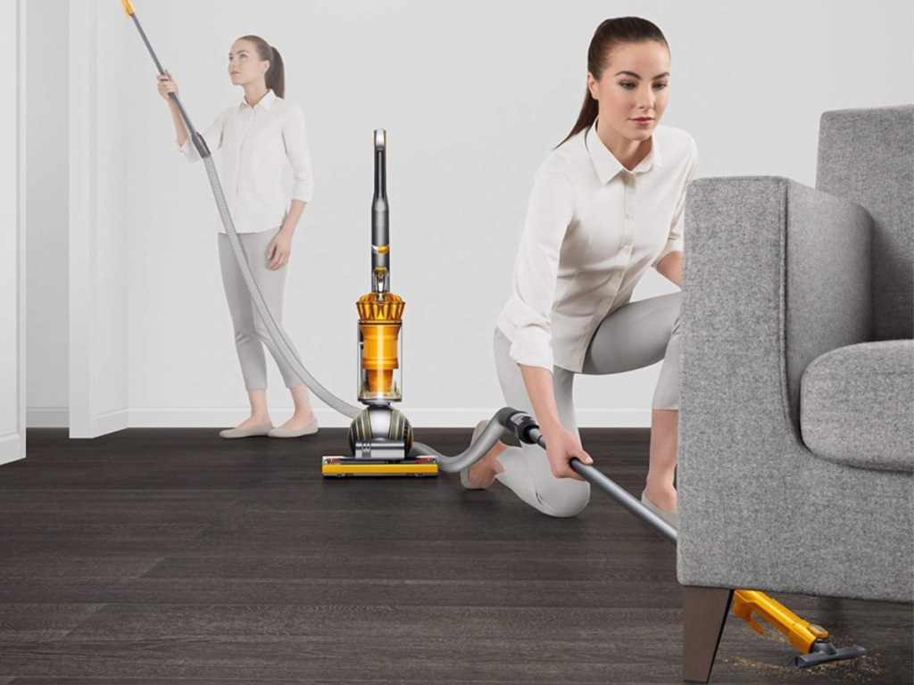 woman using cleaning wand on Dyson Ball Multi Floor 2 Upright Bagless Vacuum under couch and on wall