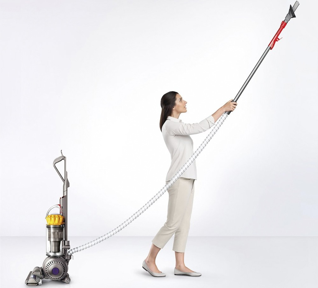 woman using dyson vacuum wand attachment to reach up high