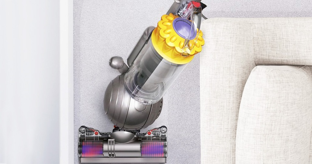 yellow and grey dyson ball vacuum cleaning around a beige colored couch