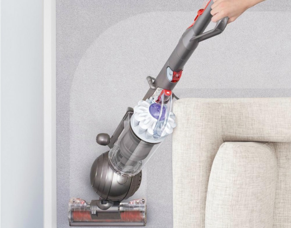 person vacuuming carpet around a couch using white dyson ball vacuum