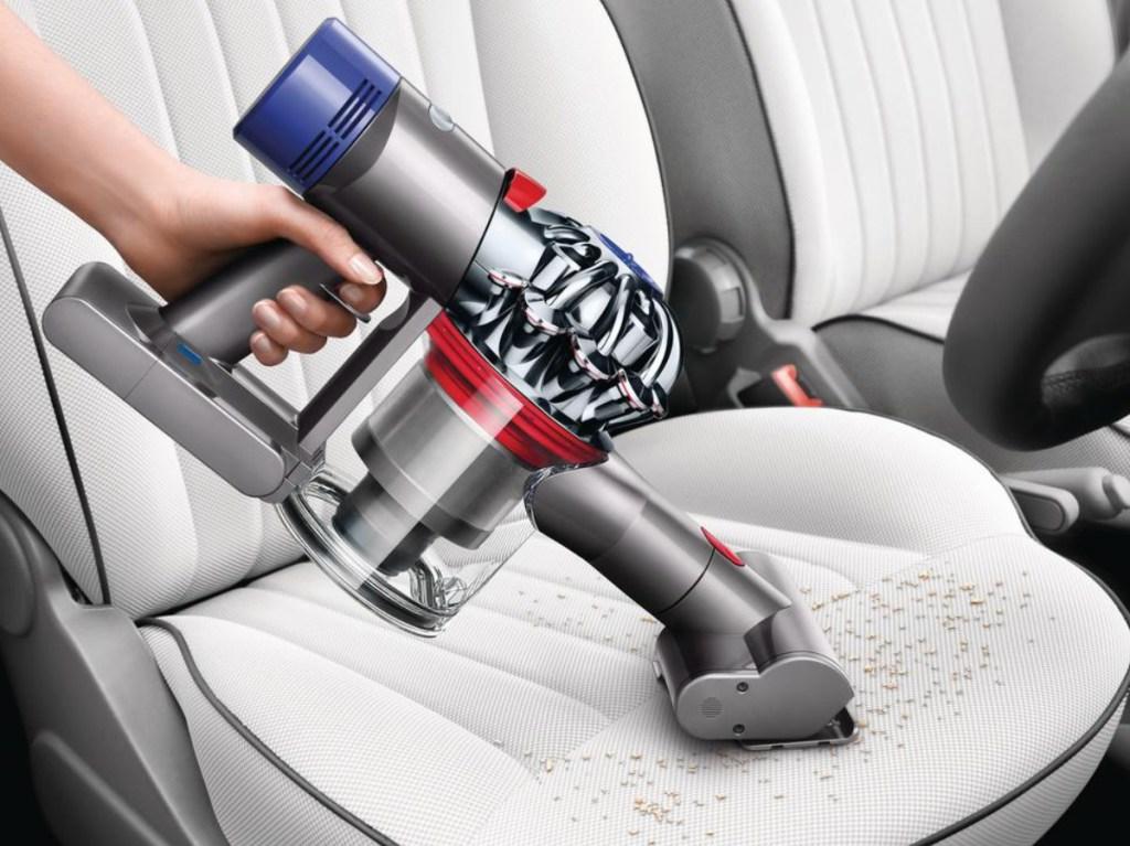 hand using cordless vacuum attachment on car seat interior