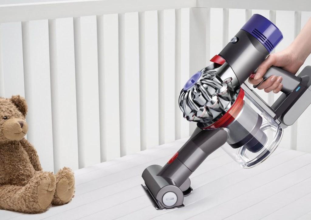 Stick Vacuum Cleaner dyson handheld vacuum vacuuming up crumbs in white baby crib