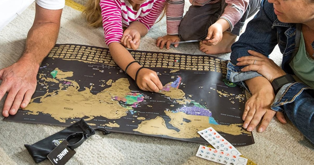 two children and two adults sitting on floor using scratch off world map
