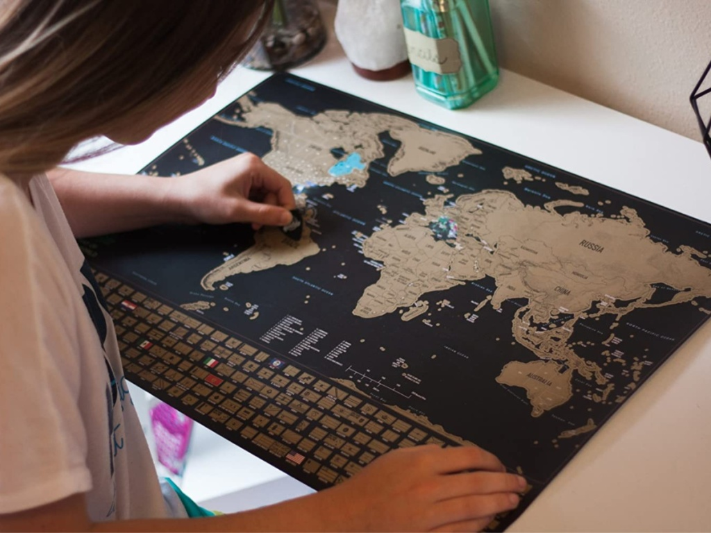 girl using scratch off world map on table