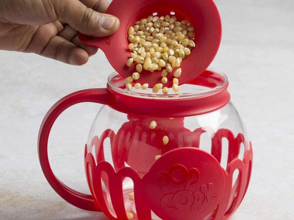 hand pouring popcorn seeds into a glass popcorn popper