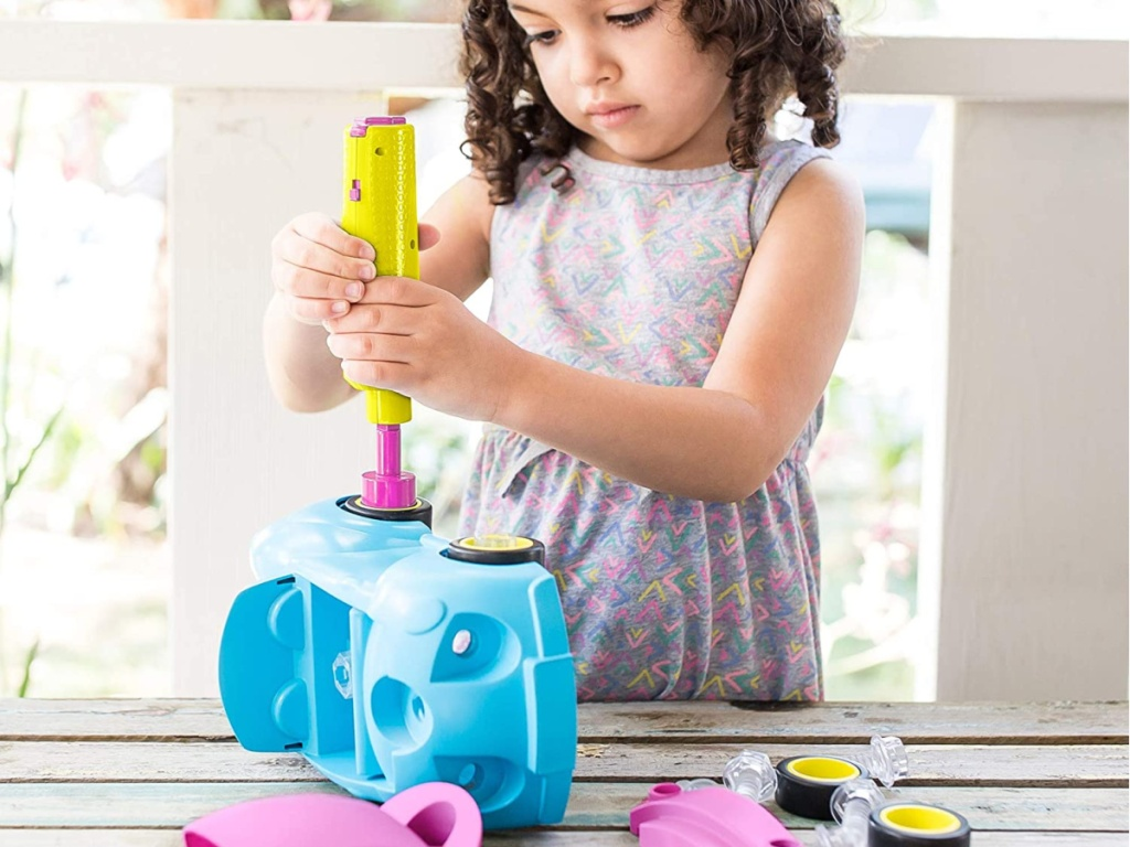 little girl using pretend drill on blue toy car