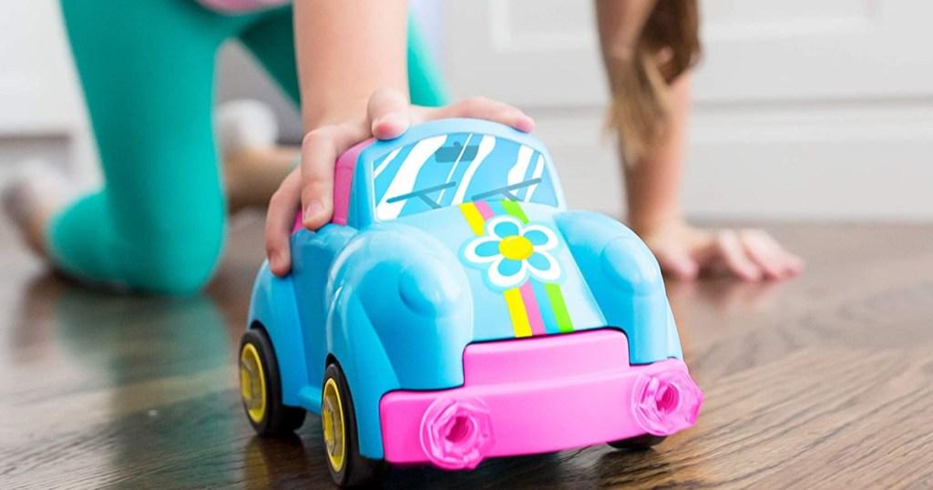 hand pushing blue flower toy car