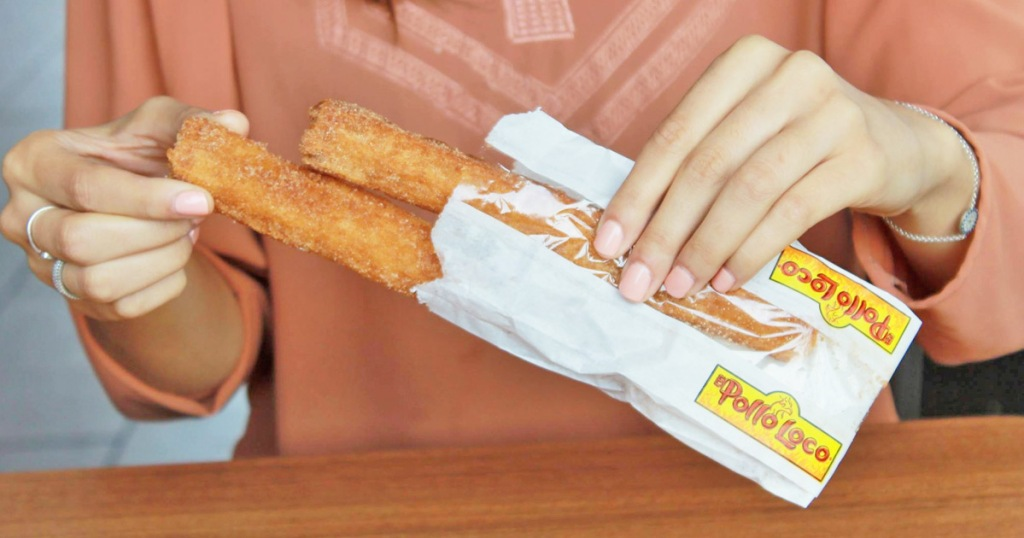 woman in pink shirt holding a white paper sleeve with two churros inside